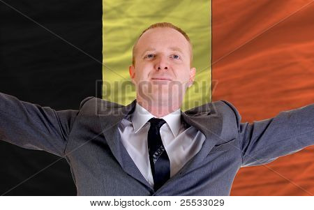 Happy Businessman Because Of Profitable Investment In Belgium Standing Near Flag