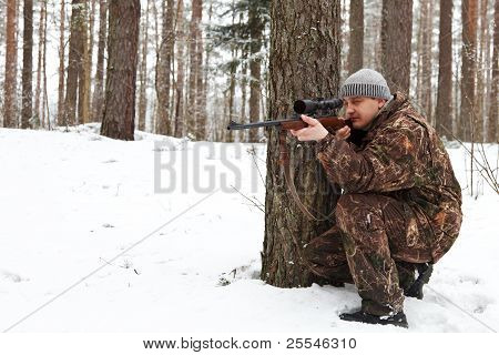 Man In Camouflage Aiming With Sniper Rifle At Winter Forest.