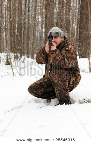 Hunter In Camouflage Aiming With Sniper Rifle At Winter Forest.