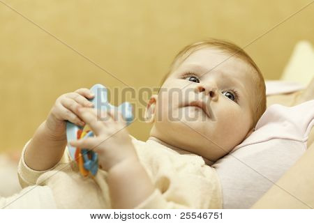 Baby With Plastic Toy In A Hand.