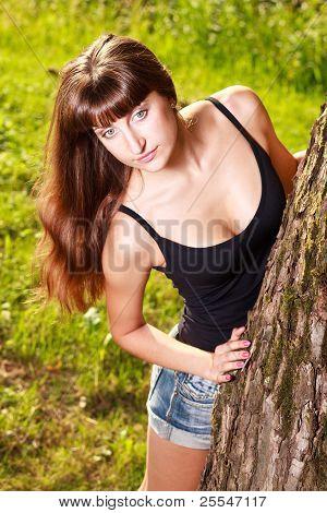 Caucasian Girl In Jeans Shorts Near A Tree Trunk.