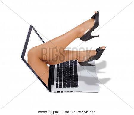 sexy legs coming out from the screen of the laptop isolated on white background