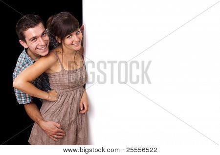 A cute couple behind a white wall 2, isolated