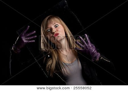 Crazy girl kissing glass, black background