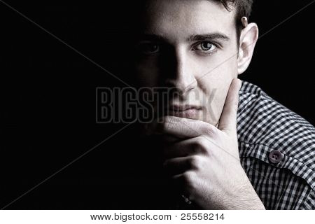 Portrait of young man thinking 2, black background