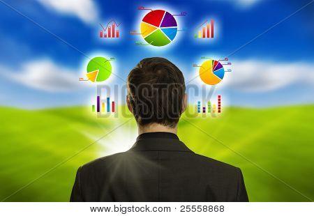 Junger Geschäftsmann mit Kreisdiagrammen seinen Kopf im Umlauf
