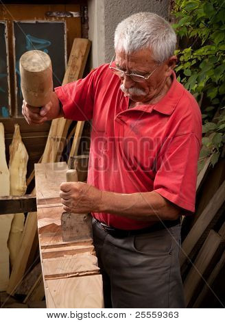 Old woodcarver working with mallet and chisel 2