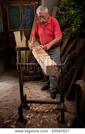 Old woodcarver working with mallet and chisel