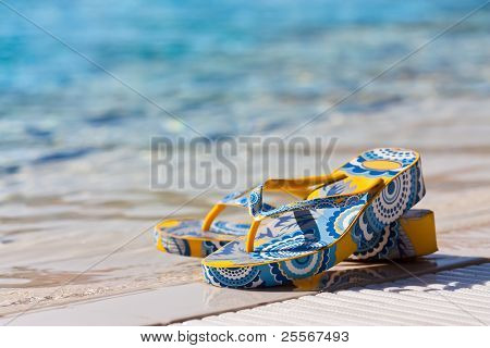 Bright flip-flops by a blue swimming pool