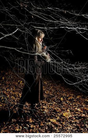 The girl in autumn dark wood among branches