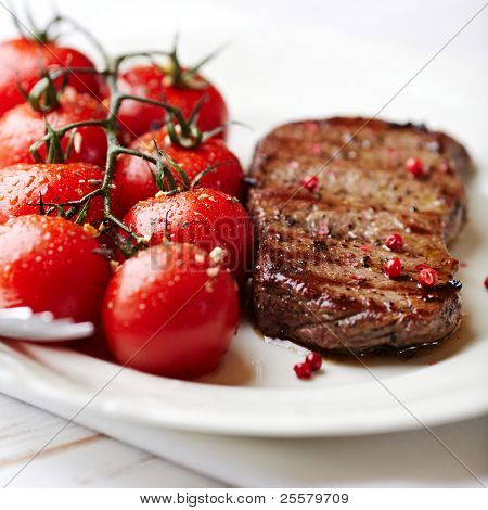 Grilled steak with cherry tomatoes on the vine