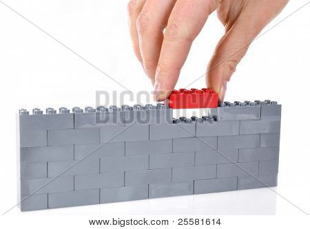 Child hand make a building of colored blocks isolated on white