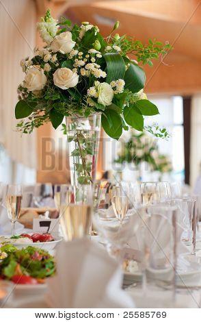 Ajuste de la tabla para un evento de boda o una cena, con flores en florero de cristal