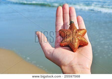 a golden christmas star on a hand on the beach