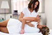 Professional Female Physiotherapist Giving Shoulder Massage To Blonde Woman In Hospital. Medical Che poster