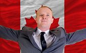 Happy Businessman Because Of Profitable Investment In Canada Standing Near Flag