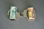 Roll Euro Money Bills (banknotes) Of 100 And 50 In Handcuffs. Euro Bills With Handcuffs. Handcuffs A poster
