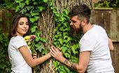 Man Bearded Hipster Holds Hand Girlfriend. Couple In Love Romantic Date Walk Nature Tree Background. poster