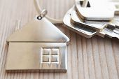 Three Keys In Key Chain With House Shaped Pendant On Natural Wood Background Closeup View With Copy  poster