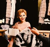 Woman With Shocked Smiling Face In Fashion Store. Girl In Pink Fur Coat Looks At Striped Fur In Male poster