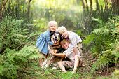 Three Happy Little Children Are Lovingly Hugging Their Adopted Pet Senior Dog, Outside In A Fern For poster