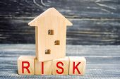 Wooden House And Cubes With The Word risk. The Concept Of Risk, Loss Of Real Estate. Property Insu poster