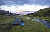 Small Green Tent Standing On Green Grass On Creek Banks Campsite Strutur Near Road F210, Snow Patche poster