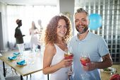 Young cheerful couple with drinks in wineglasses cheering up while looking at camera at party poster