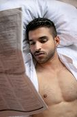 Man In Bed With Open Shirt And Pecs Sleeps Reading Newspaper poster