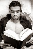 Man In Bed With Open Shirt And Pecs Reading Hardback Book poster