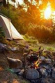 Old Small Kettle Is Heated On A Bright Bonfire On A Green Mountain Meadow Next To Tent In The Rays O poster