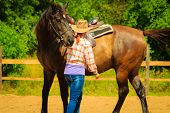 Taking Care Of Animals, Horsemanship, Equine Concept. Cowgirl Getting Horse Ready For Ride On Countr poster