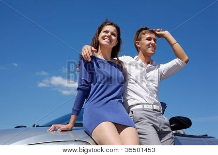Young smiling couple stands leaning on car on background of blue sky
