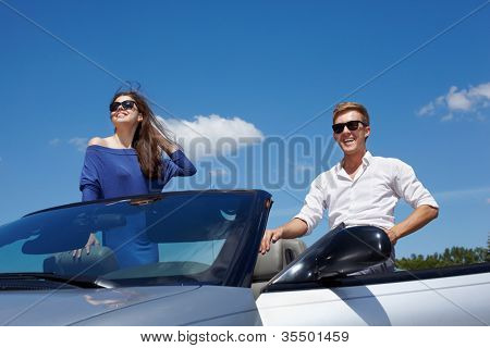 Young girl and her boyfriend in dark sunglasses in cabriolet look at sun and smile