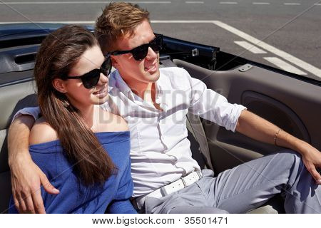 Young couple in dark sunglasses sits having embraced in a cabriolet on back seats