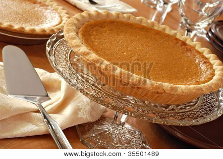Elegant still life of pumpkin pie on antique pedestal plate with pie server and dinnerware.  Closeup with shallow dof.