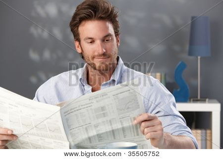 Handsome man sitting in living room, reading newspaper, smiling.