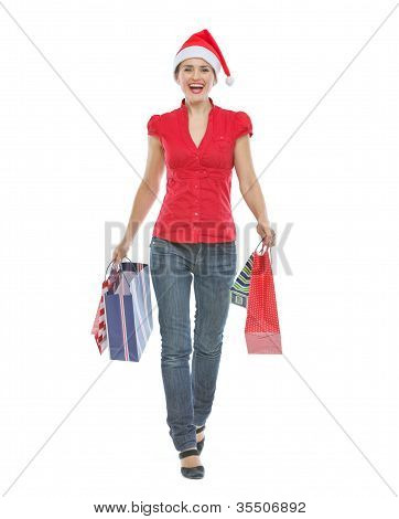 Happy Woman In Christmas Hat With Shopping Bags Making Step Forw