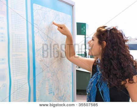 Brunet Female Smiling And Pointing At A Map