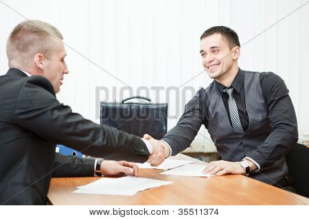Young Business Man Shaking Hands With Colleague Across The Table