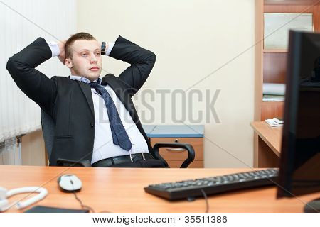 Portrait Of Relaxed Business Man Sitting At His Desk And Thinking About Something