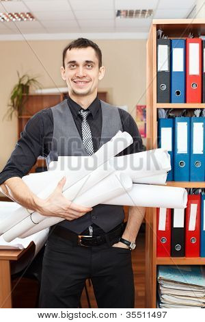 Handsome Male Business Executive Standing With Rolled Blueprints In Hands
