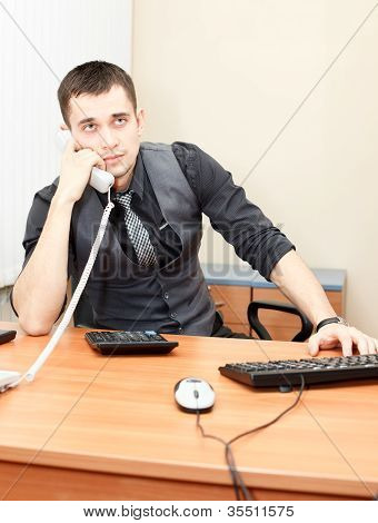 Smart Businessman Speaking On Phone While Working On Desktop Computer