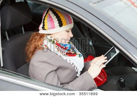 Young Caucasian Woman Sitting In Car On Passenger Seat And Holding Electronic Device