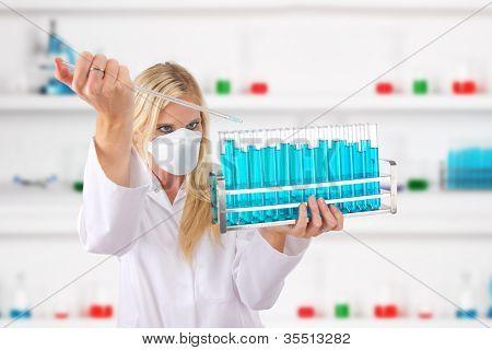 Ayudante de laboratorio atractivas jóvenes que caen químicos líquidos en frascos de cristal