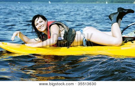 Smiling girl lies on surfing