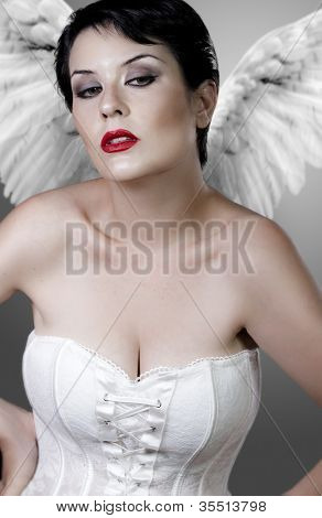 Beautiful sad angel with white corset and light wings, underwear