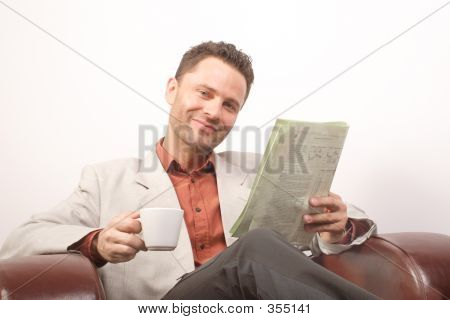 Smiling Handsome Man With Newspaper And Cup Of Coffee