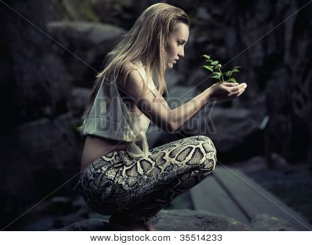 Beautiful young woman holding a plant