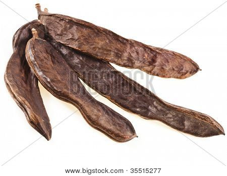Ripe carob pods or St. John's bread isolated on white background